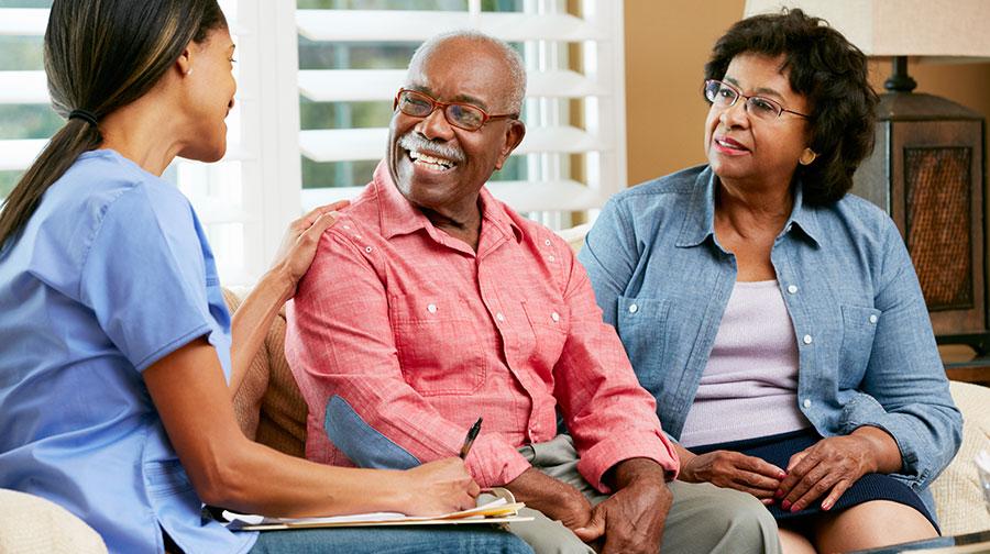 Senior couple speaking with caregiver